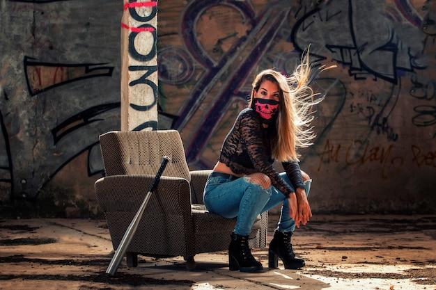 오래 된 소파를 사용 하여 버려진 공장에 분홍색 입 마스크와 위험한 소녀.