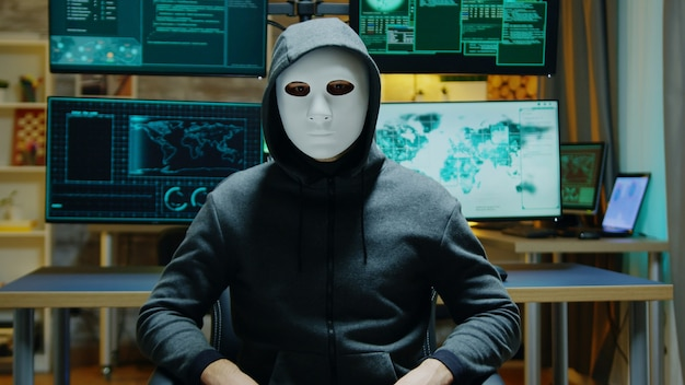 Dangerous hacker hiding his identity wearing a white mask while using augmented reality to steal confidential data.