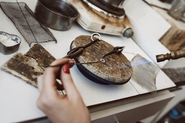 위험한 직업. 보석 제작 워크샵에서 용접 토치에서 불꽃으로 은 귀걸이를 납땜하는 보석상의 손의 상위 뷰.