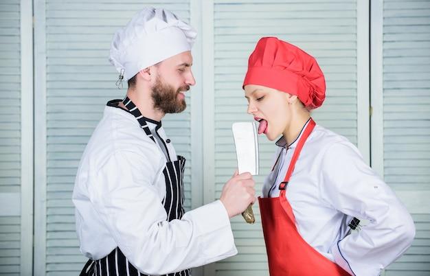 危険な舐めシェフが包丁ナイフツールを握り、女性が刃を舐める料理はセクシーシャープナイフ