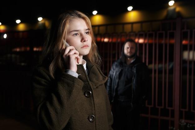 Опасный мужчина и молодая женщина на улице