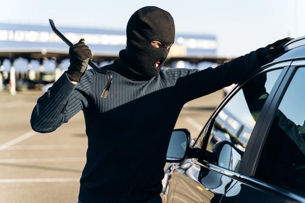 검은 옷을 입은 위험한 남자가 머리에 발라클라바를 하고 도둑질하기 전에 지렛대로 차 한 잔을 깨려고 준비합니다. 자동차 도둑, 자동차 절도 개념