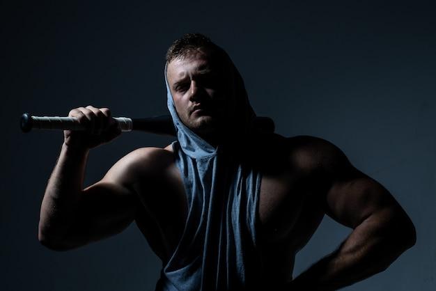戦いの準備ができている野球のバットを持つ危険な筋肉の男。