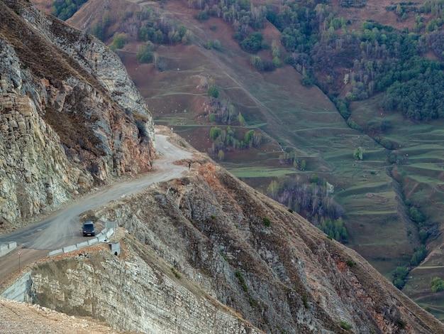 危険な狭い崖の山道。山の端と急な崖に沿って運転する危険なオフロード。ダゲスタン。