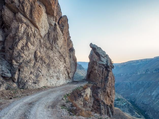 鋭い岩を通る危険な狭い崖の山道..山の端と急な崖に沿って運転する危険なオフロード。ダゲスタン。