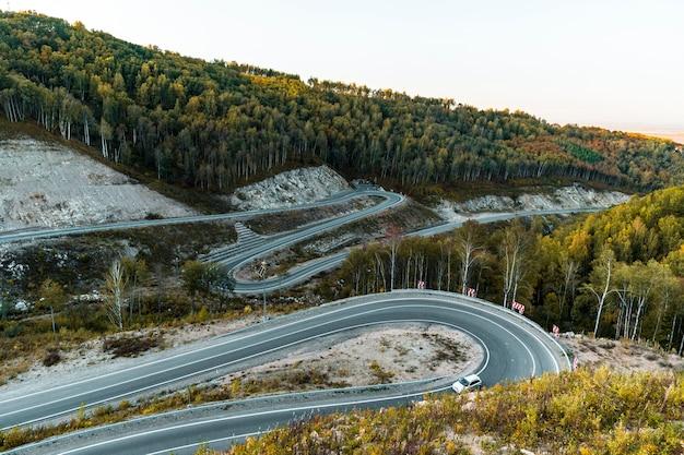 Опасная дорога в районе курортного города белокуриха. серпантинная дорога в горах алтая в яркий солнечный день, внизу зеленая трава и асфальтированная дорога с крутым поворотом, оставляющим за собой гору