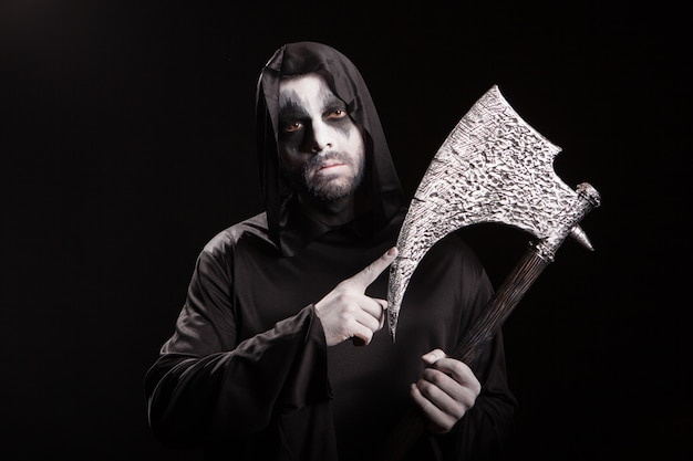 Dangerous scary man dressed up like grim reaper with an axe over black background.