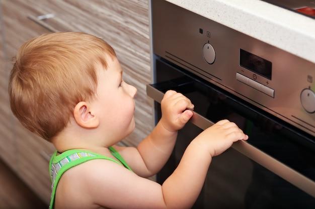 キッチンの危険な状況。電気オーブンで遊んでいる子供。