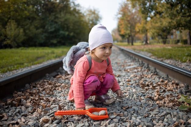 아이들과 위험한 상황. 귀여운 유아 아기 소녀는 혼자 철도 트랙에 앉는다.