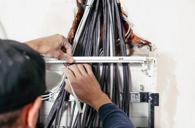 電気による危険な作業電気技師は電気パネルを設置し、ワイヤーを準備します