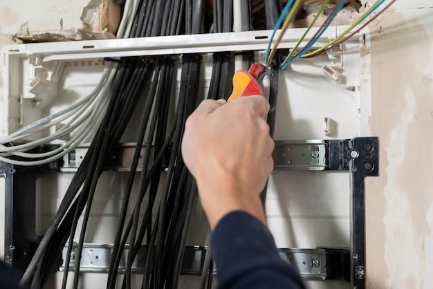 電気の危険な作業電気技師は電気パネルを設置し、ワイヤーを準備します