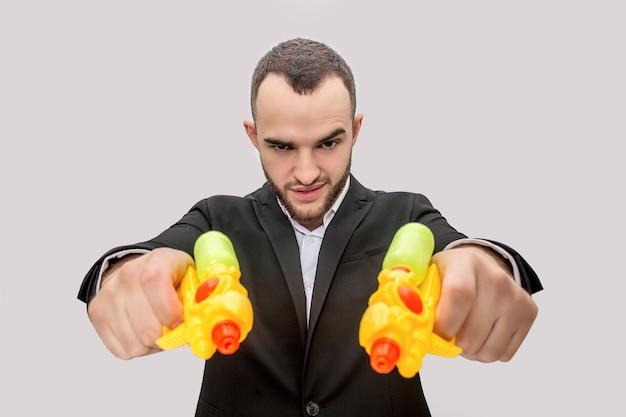 정장을 입은 위험한 청년이 두 개의 물총을 손에 들고 똑바로 지시합니다.