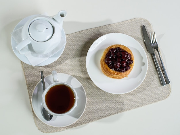 Danish cake with cherries and black tea on a table in a cozy coffee shop