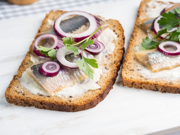 Danish open sandwich smorrebrod with salted herrings, red onion, butter.