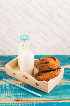 Danish pastries with milk bottle on wooden tray near straw over blue wooden table