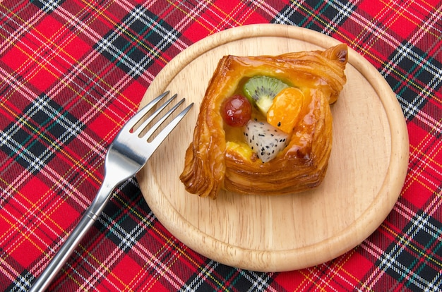 Danish pastry with fruits on red fabric plaid