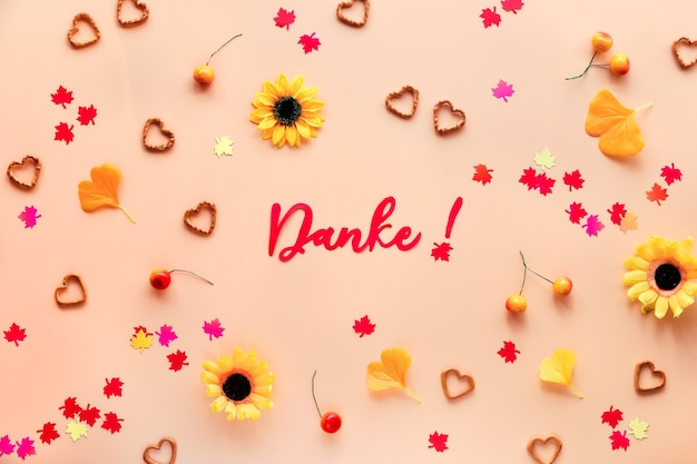 Danke means thank you in german language. fall decorations - yellow flowers, orange gingko leaves, maple leaf paper confetti