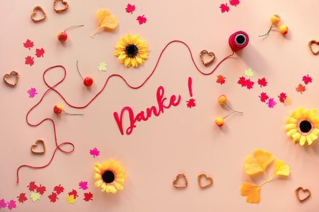 Данке означает «спасибо» на немецком языке. осенние украшения - желтые цветы, оранжевые листья гинкго, бумажное конфетти из кленовых листьев