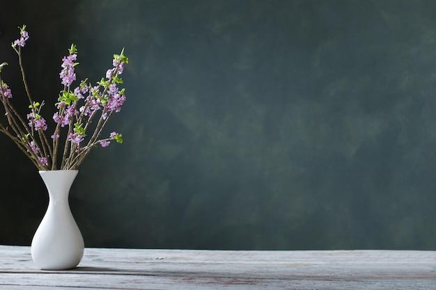 녹색 배경 벽에 오래 된 나무 테이블에 꽃병에 다프네 꽃