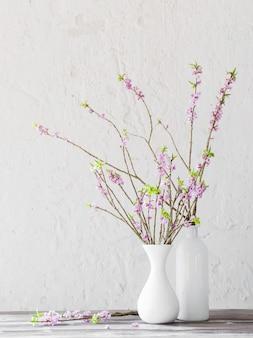 背景の白い壁の古い木製のテーブルの花瓶にジンチョウゲの花