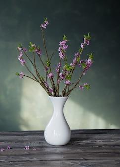 古い木製のテーブルの上の花瓶にジンチョウゲの花