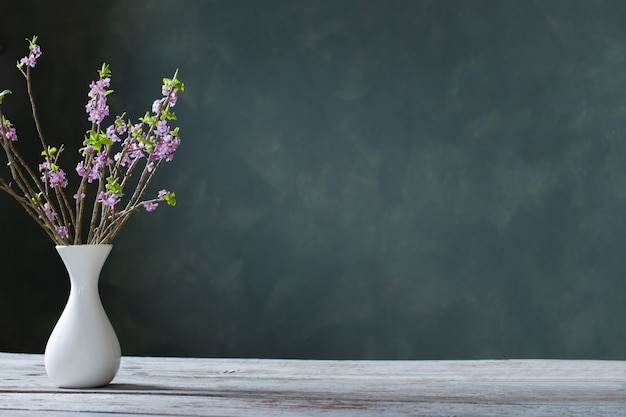 Daphne flowers in vase on old wooden table on background green wall