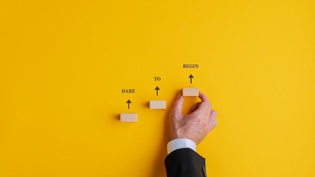 木製のペグで作られた階段の上に書かれたサインをあえて始めてください。黄色の背景の上。
