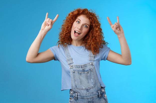 大胆なクールでスタイリッシュな素晴らしい赤毛の陽気な縮れ毛の女の子の傾きの頭のショーの舌は楽しい青い背景を持つカメラの遊び心のあるレイズハンドロックンロールヘビーメタルジェスチャーを喜んで見つめます。
