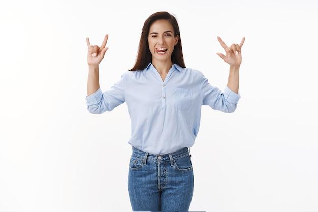 Audace donna adulta di bell'aspetto con un tatuaggio in camicia blu da ufficio, sentendosi rock-n-roll, godersi la festa dei colleghi, uscire la sera, mostrare segni di metalli pesanti ammiccano impertinenti, stare in piedi su un muro bianco esultando