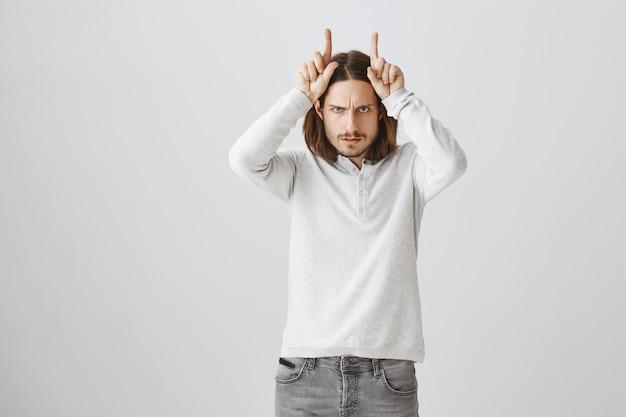 Ragazzo audace accigliato, mostrando il gesto delle corna del diavolo