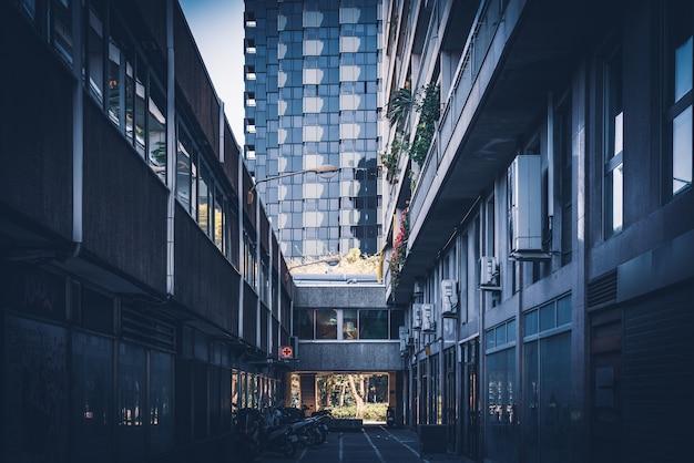 現代都市の暗い路地と近代的な建物