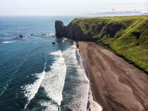 Темный, почти черный цвет песчаный пляж тихого океана. каменные горы и желтая трава на заднем плане. голубое небо.