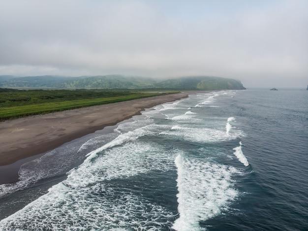 태평양의 어두운 거의 검은 색 모래 해변. 돌 산과 노란 잔디가 배경에 있습니다.