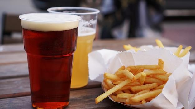 木製のテーブルフードコートの持ち帰り用食品のダークとライトのビールとフライドポテト