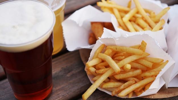 나무 테이블에 어둡고 가벼운 맥주와 감자 튀김 푸드 코트 테이크 아웃 음식
