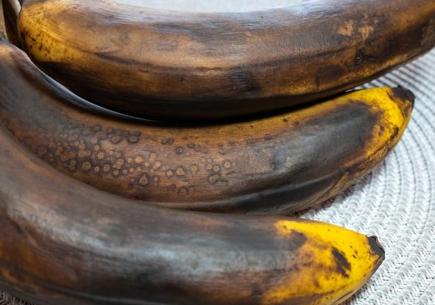 Темный и испорченный банан на столе. гнилые фрукты.