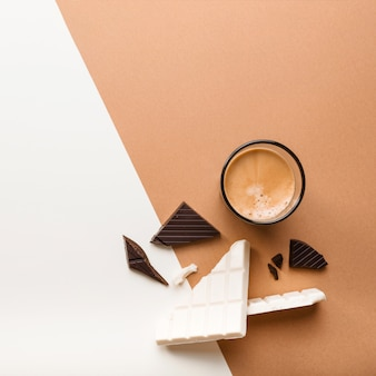 Dark and white chocolate bar with coffee glass on dual backdrop