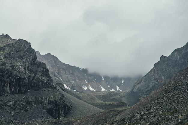 비오는 날씨에 높은 고도에 어두운 계곡에 회색 낮은 구름과 어두운 대기 산 풍경. 회색 흐린 하늘에 낮은 구름에 눈이 있는 큰 바위 산 벽. 우울한 산 풍경