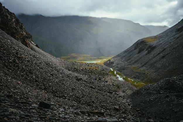 Темный атмосферный вид от кулуара с ручьем до зеленой горной долины с озером в пасмурную погоду. дождливый горный пейзаж с опасными горами под серым небом. горный перевал в дождливую погоду.