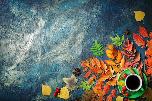 Dark autumn background with cup of coffee and autumn leaves.