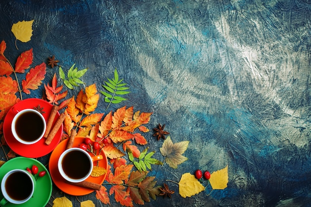 Dark autumn background with cups of coffee and autumn leaves.