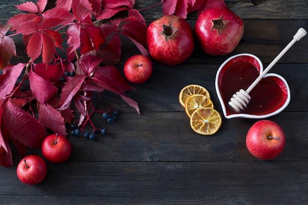 On a dark background apples, pomegranates, lemon slices, honey in a vase - a background ab
