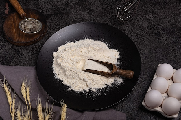 Dark background for baking with eggs, flour, wheat, whisk