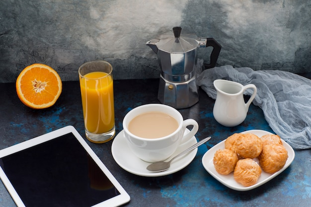 On a dark background coffee with milk, cakes, coffee pot, tablet, gauze as a decor and a glass with orange juice