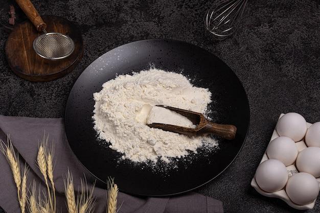 卵、小麦粉、小麦、泡立て器で焼くための暗い背景