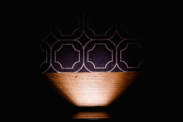 Dark background illuminating the floor carpet by a lamp, copy space.
