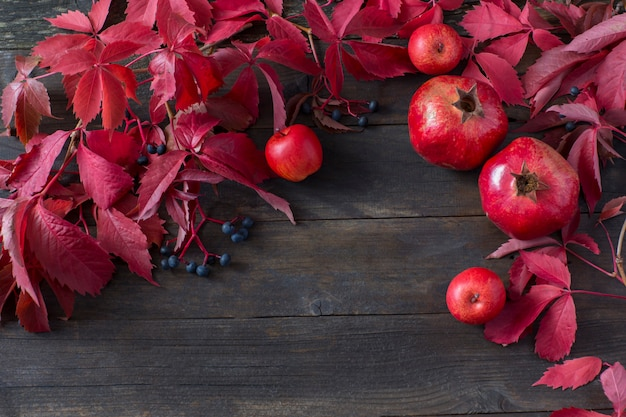 On a dark background pomegranates, apples and autumn leaves - autumn background