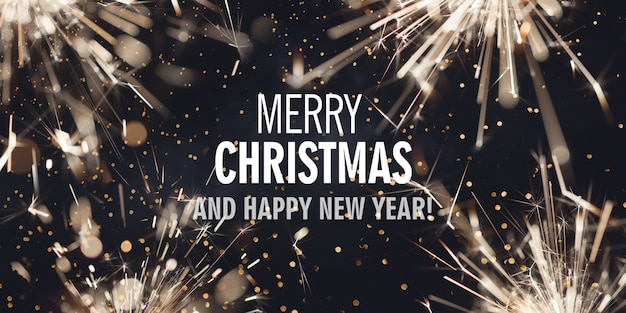 Темный фон с горящими бенгальскими огнями и текстом с рождеством и новым годом