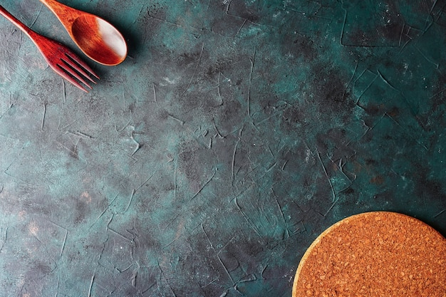 台所用品の木のスプーンとテキストメニューのフォークコピースペースと暗い背景