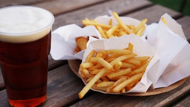 Темное пиво и картофель на деревянном столе еда на вынос фуд-корт